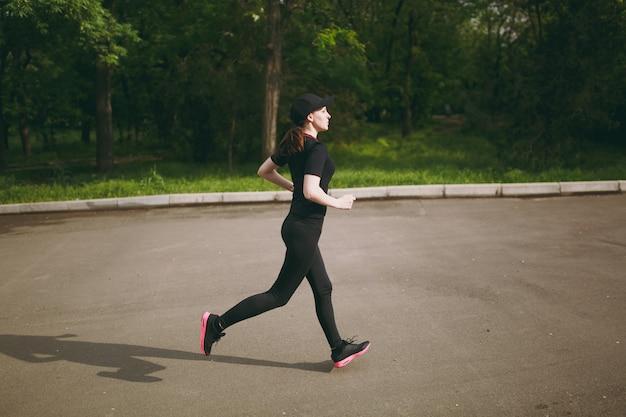 Seitenansicht junges athletisches brünettes mädchen in schwarzer uniform und mützentraining, sportübungen und laufen, direkt auf den weg im stadtpark im freien schauend