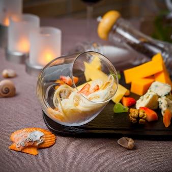 Seitenansicht käse mit glas und kerzen in holzteller gesetzt