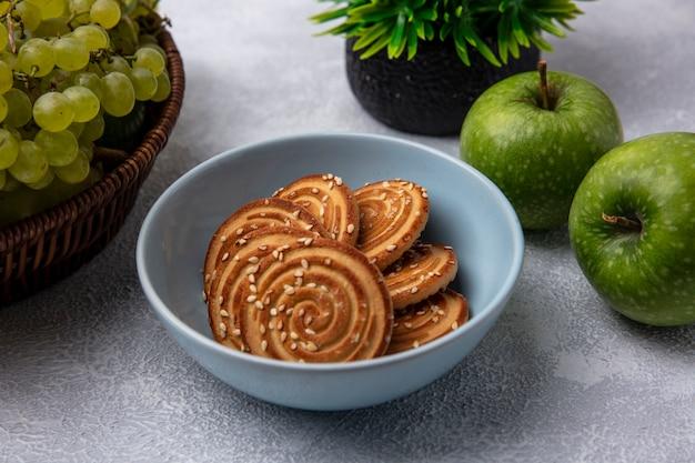 Seitenansicht-kekse in einer schüssel mit grünen äpfeln und grünen trauben auf einem weißen hintergrund
