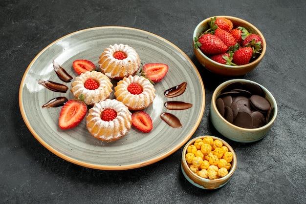 Seitenansicht kekse mit süßigkeiten kekse mit schokolade und erdbeere neben schalen mit haselnüssen erdbeere und schokolade auf dem tisch