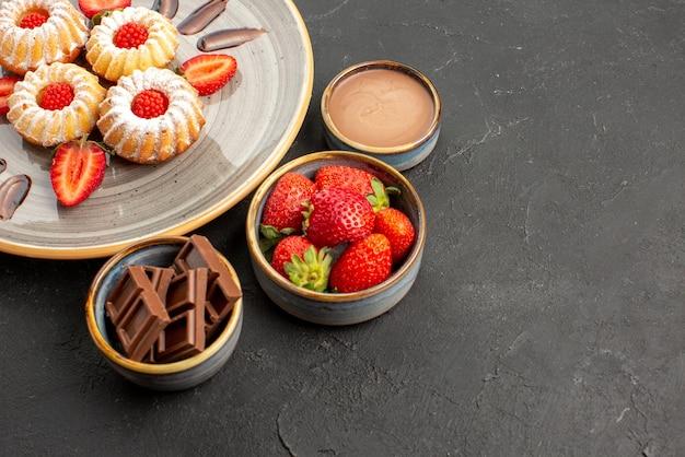 Seitenansicht kekse und erdbeeren appetitliche kekse mit erdbeeren auf dem teller neben schüsseln mit erdbeerschokolade und schokoladencreme auf dem tisch