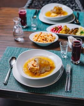 Seitenansicht khash mit eingelegtem gurken-hartriegel-kirschpflaumen-auberginenessig und brot zwieback auf dem tisch