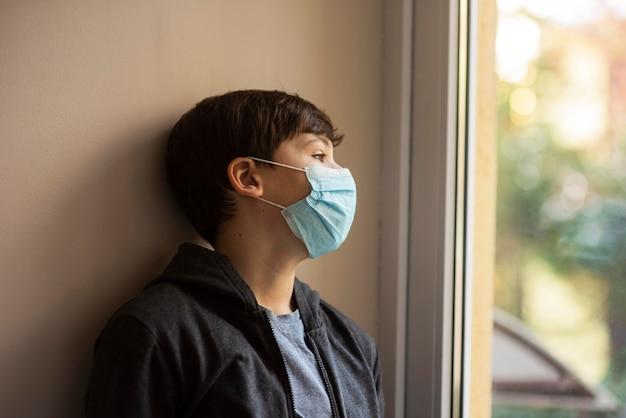 Seitenansicht kleiner junge mit der medizinischen maske, die weg schaut