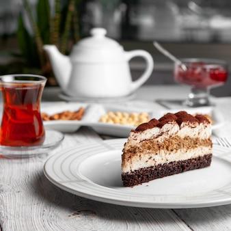 Seitenansicht köstliches dessert in platte mit tee, nüssen, teekanne, fruchtmarmelade auf weißem hölzernem hintergrund.