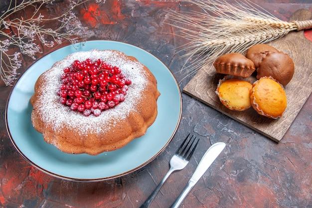 Seitenansicht kuchen cupcakes vier cupcakes ein kuchen mit roten johannisbeeren messergabel weizenähren