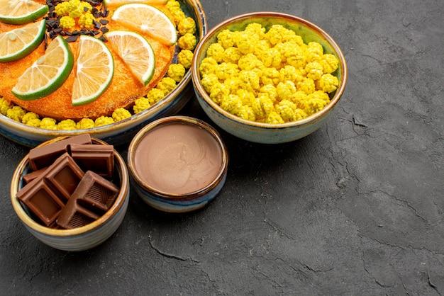 Seitenansicht kuchen und süßigkeiten appetitlicher kuchen mit limette und schalen mit süßigkeiten schokolade und schokoladencreme auf dem schwarzen tisch
