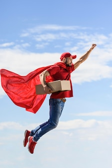 Seitenansicht-lieferbote, der superheldenumhang trägt