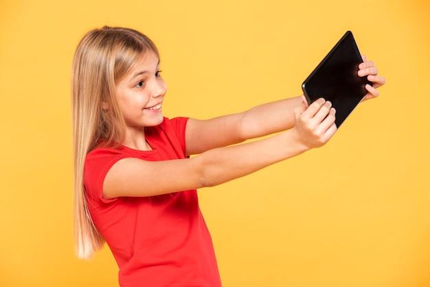 Seitenansicht-mädchen, das auf tablette spielt