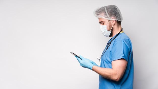 Seitenansicht männliche krankenschwester, die tablette durchsucht