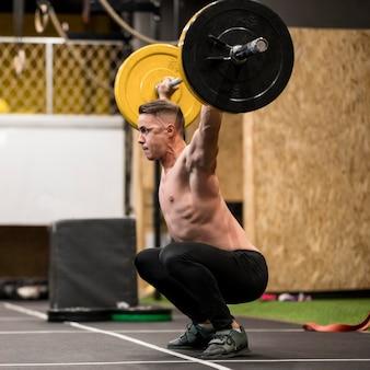 Seitenansicht männliches training mit gewichtheben