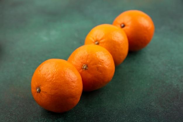 Seitenansicht mandarinen auf einem grünen hintergrund