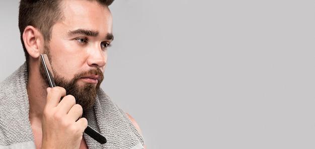 Seitenansicht-mann, der seinen bart mit kopienraum rasiert
