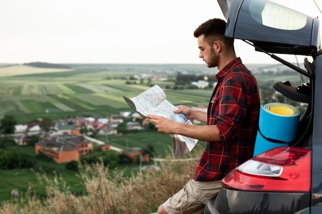 Seitenansicht mann im auto, das karte liest