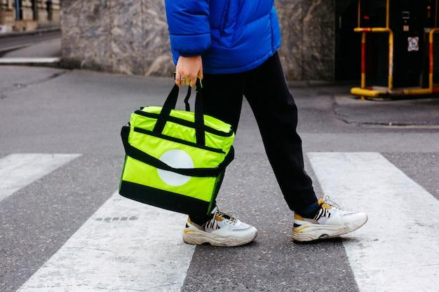 Seitenansicht mann trägt ordnung in hellgrüner tasche auf fußgängerzebra-straße