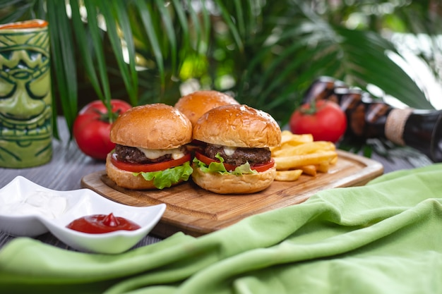 Seitenansicht mini burger rindfleisch pastetchen tomaten salat käse ketchup und pommes frites auf einem brett
