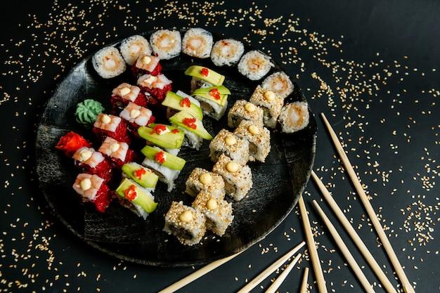 Seitenansicht mischen sushi-rollen auf einem teller mit wasabi-ingwer und essstäbchen mit sesam auf einem schwarzen hintergrund