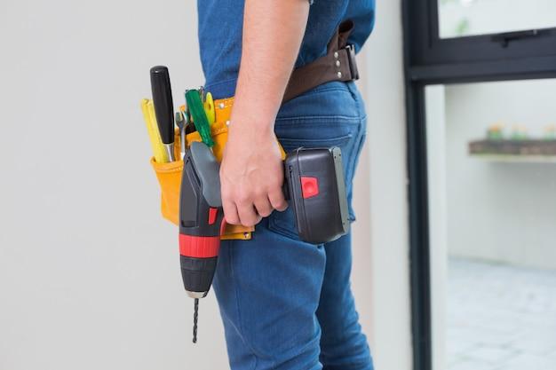 Seitenansicht mittlerer abschnitt eines heimwerkers mit bohrmaschine und werkzeuggürtel