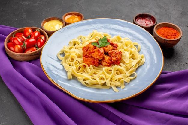 Seitenansicht nudeln und soßen blauer teller mit nudelkräuterfleisch und soße zwischen tomaten und bunten soßen in schalen auf der lila tischdecke