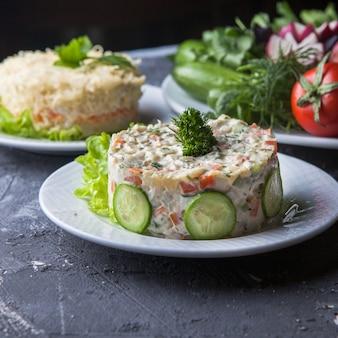 Seitenansicht oliviersalat mit mimosensalat und tomate und gurke in rundem weißem teller