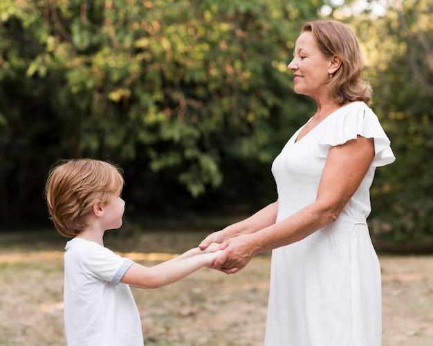 Seitenansicht oma und kind händchen haltend