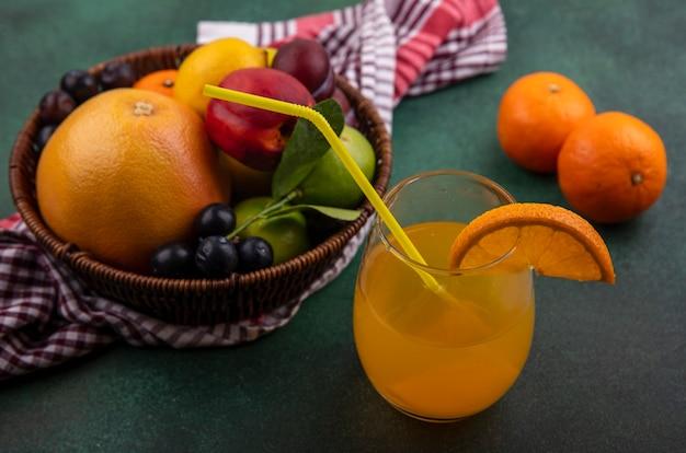 Seitenansicht orangensaft in einem glas mit grapefruit limette zitronenpfirsich kirschpflaume orange und pflaume in einem korb auf einem grünen hintergrund