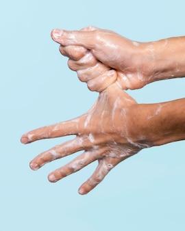 Seitenansicht person, die hände auf blau isoliert wäscht
