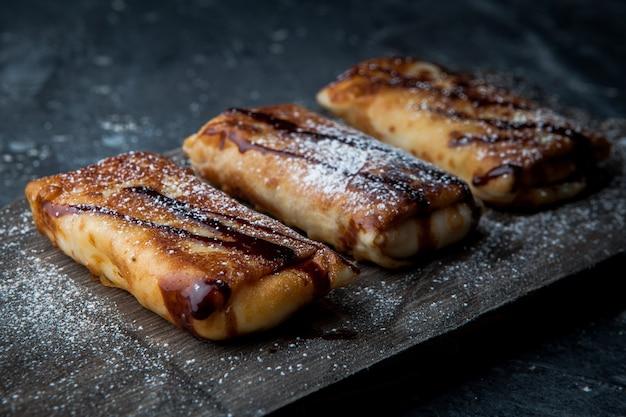 Seitenansicht pfannkuchen mit schokoladensirup und puderzucker im schneidebrett