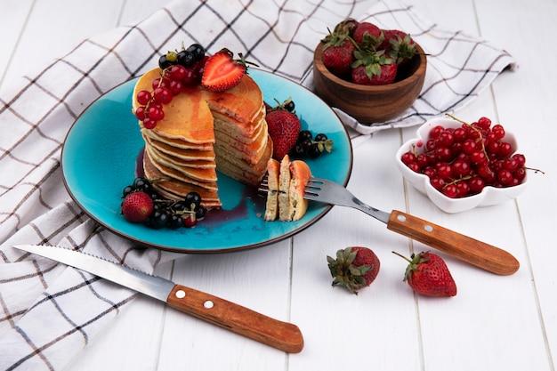 Seitenansicht pfannkuchen mit schwarzen und roten johannisbeeren erdbeeren mit einer gabel und einem messer auf einem teller auf einem weißen karierten handtuch