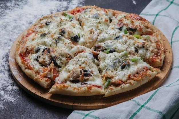 Seitenansicht pizza auf einem holzständer mit einer tischdecke horizontal