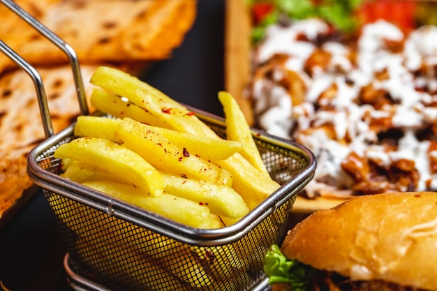 Seitenansicht pommes frites im edelstahl-minikorb mit salz und burger auf dem tisch