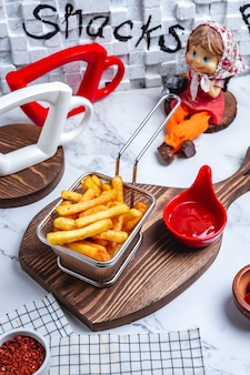 Seitenansicht pommes frites in einem korb mit ketchup auf dem brett