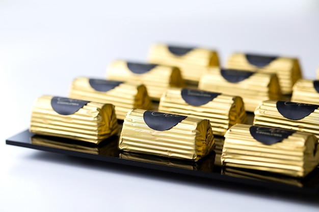 Seitenansicht praline in einer goldverpackung auf schwarzem ständer