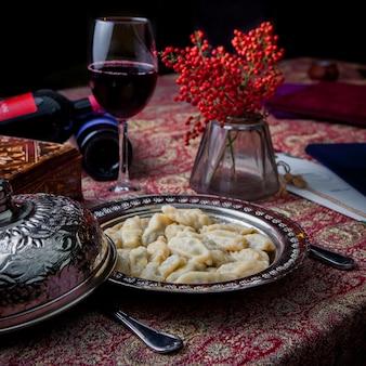 Seitenansicht qurza mit ebereschenfrüchten und rotwein in kupferplatte