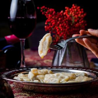 Seitenansicht qurza mit ebereschenfrüchten und rotwein und menschlicher hand und gabel in kupferplatte