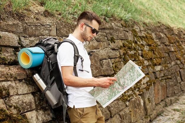 Seitenansicht reisender, der karte liest