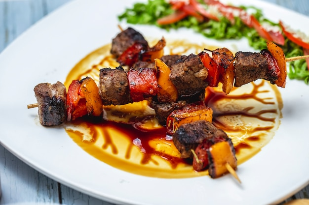 Seitenansicht rindfleischspiesse gegrilltes rindfleisch mit roten und gelben tomatenpaprika und sauce auf einem teller