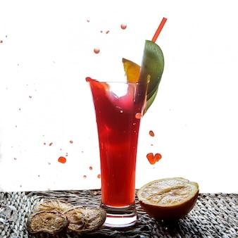 Seitenansicht roter fruchtsmoothie mit tubuli für getränke und halbe orange und tropfen in servietten