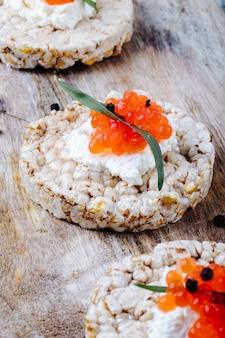 Seitenansicht rotes kaviar vorspeise knuspriges knäckebrot mit hüttenkäse rotem kaviar tarhun und schwarzem pfeffer auf einem brett