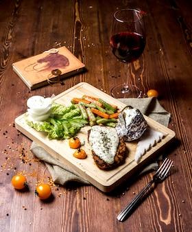 Seitenansicht schnitzel mit frischkäse mit ofenkartoffeln in folie und mit gemüse auf einem brett und einem glas rotwein