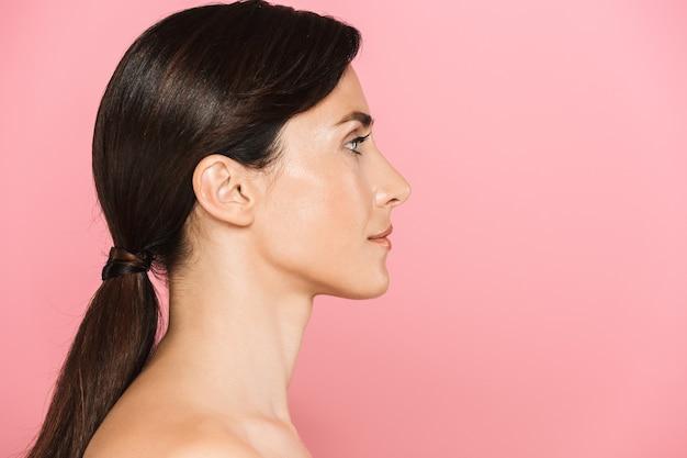 Seitenansicht schönheitsporträt einer attraktiven sinnlichen brünetten oben ohne frau, die isoliert steht