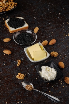 Seitenansicht schwarzkaviar weißbrot mit hüttenkäse schwarzkaviar butter mandel und walnuss auf schwarzer oberfläche
