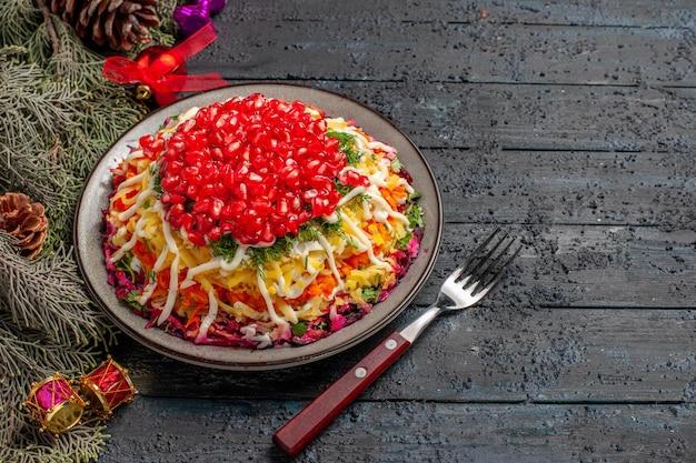 Seitenansicht teller appetitliche tellergabel und fichtenzweige mit zapfen und weihnachtsbaumspielzeug