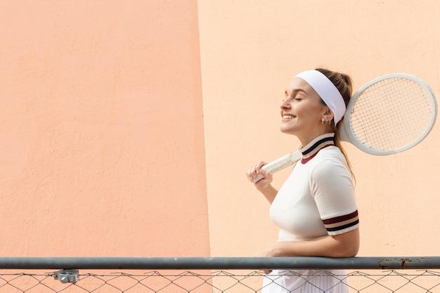 Seitenansicht-tennisspielerfrau mit schläger