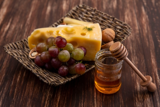 Seitenansicht trauben mit sorten von käse und nüssen auf einem stand mit honig in einem glas auf einem hölzernen hintergrund