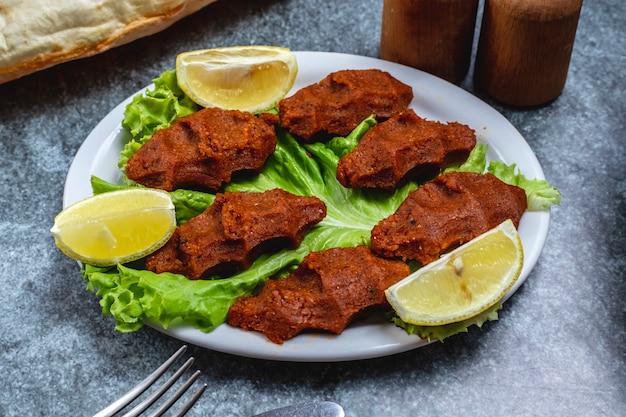 Seitenansicht vegetarisches steak zahnsteinbällchen mit zitronenscheiben auf salatblatt