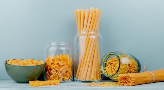 Seitenansicht verschiedener arten von makkaroni als bucatini-spaghetti-fadennudeln und andere auf holzoberfläche und blauem hintergrund