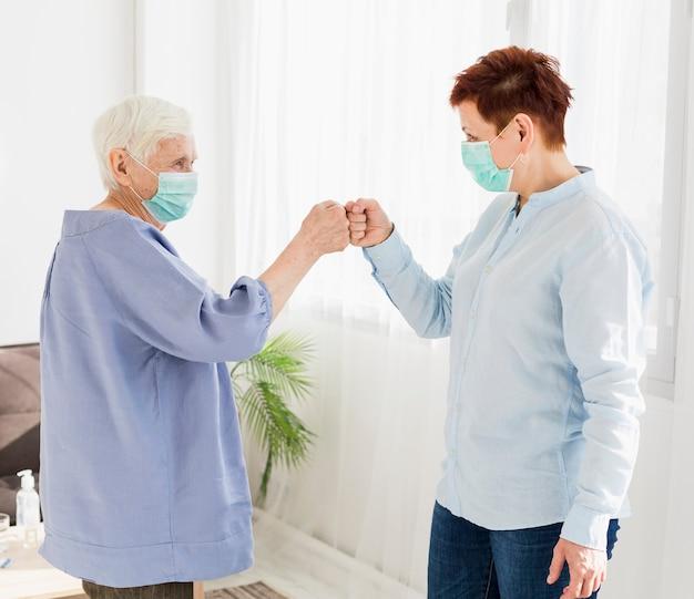Seitenansicht von älteren frauen, die fäuste stoßen, während sie medizinische masken tragen