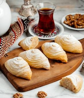 Seitenansicht von aserbaidschan traditionellem gebäckplätzchen badambura auf holzbrett serviert mit tee