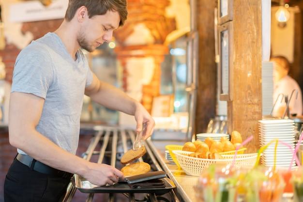 Seitenansicht von auswahlfrühstücksbestandteilen des jungen mannes im straßencafé