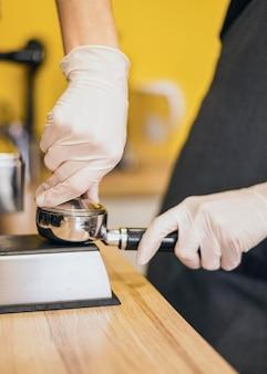 Seitenansicht von barista mit handschuhen, die kaffee für maschine vorbereiten